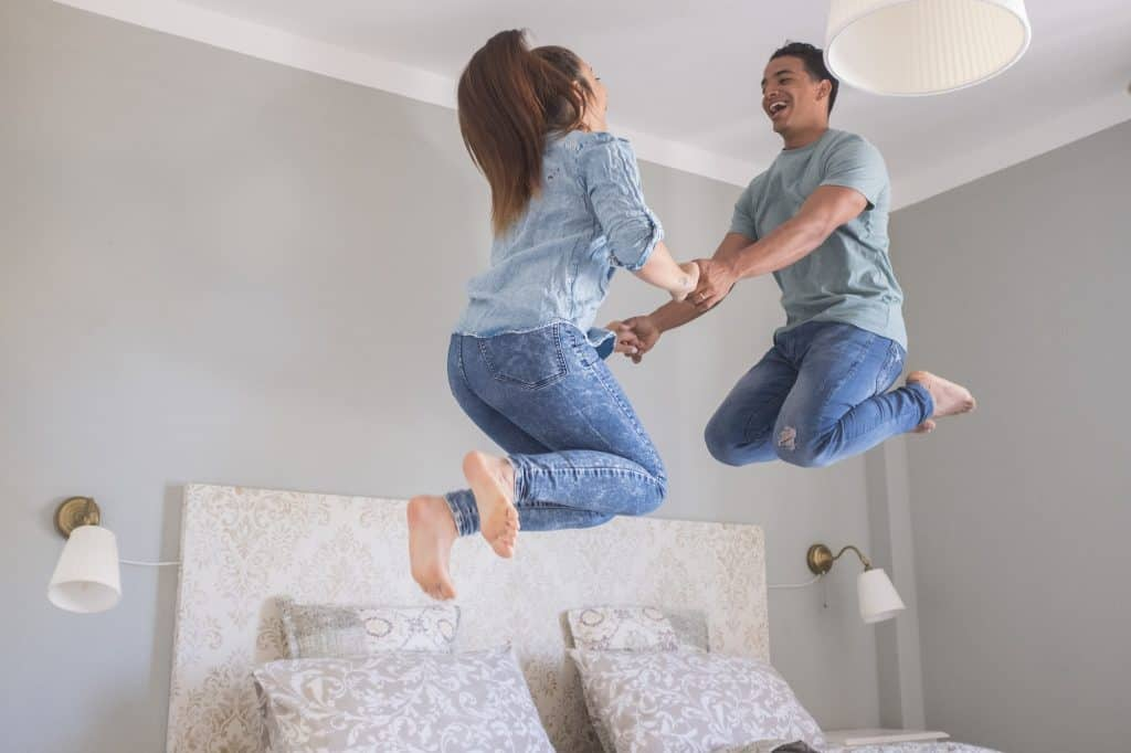 Young couple love life together at home and jump in the air in the bedroom - new house buy